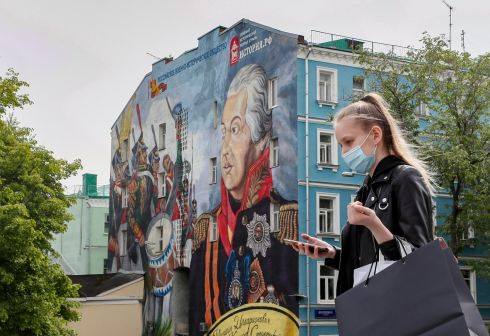 MOSCOW MASK: A woman wearing a face mask walks past a mural of the Russian commander Mikhail Kutuzov in Moscow, Russia. Coronavirus restrictions in the city will be eased from June 1st. Photograph: Yuri Kochetkov/EPA