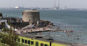 AT BAY: Crowds gather to enjoy the good weather at Seapoint in Co Dublin. Photograph: Nick Bradshaw/The Irish Times