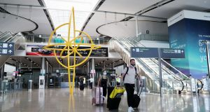 People wearing protective face masks walk through Terminal 2 in Dublin Airport. Photograph: Brian Lawless/PA Wire
