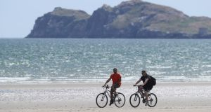 Cyclists on Portmarnock Beach on Friday, as the warm weather continues. Reopening – and restarting economic activity – will involve risk. But so does every other course of action. Photograph: Brian Lawless/PA Wire
