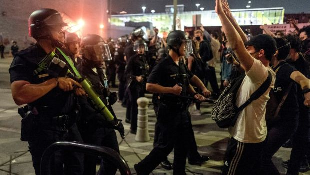 Protesters confront police officers during a protest over the death of George Floyd. Photograph: AP