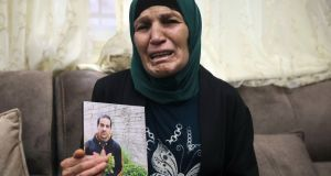 Rana, mother of Iyad Halak (32), holds his photo at their home in East Jerusalem. Israeli police shot dead Mr Halak near Jerusalem's old city. He was unarmed, according to Israeli media reports. Photograph: Mahmoud Illean/AP