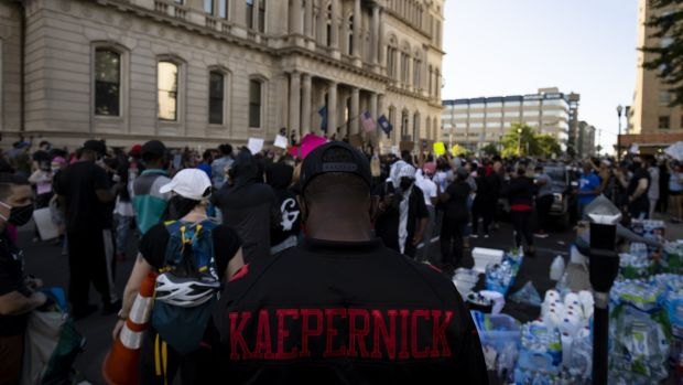 A protestor wears a Colin Kaepernick jersey as he and others gather outside city hall in Louisville, Kentucky on Friday. Photo: Brett Carlsen/Getty Images