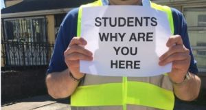 A resident holding a sign protesting at students returning to their rented accommodation in Cork.
