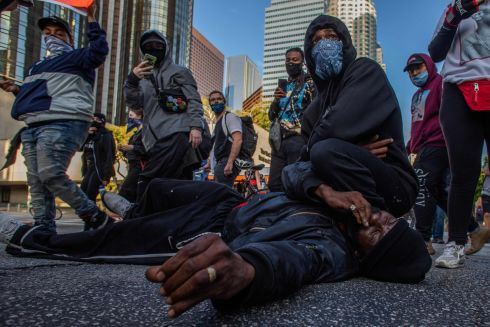 "UNDER BENDED KNEE: Demonstrators in Los Angeles, US, simulate the death of George Floyd, a black man who died while being arrested and pinned to the ground under the knee of a Minneapolis police officer. Overnight clashes continued and major cities imposed curfews, as angry demonstrators ignored warnings from President Donald Trump that his government would stop violent protests over police brutality ""cold"". Photograph: Apu Gomes/AFP/Getty"
