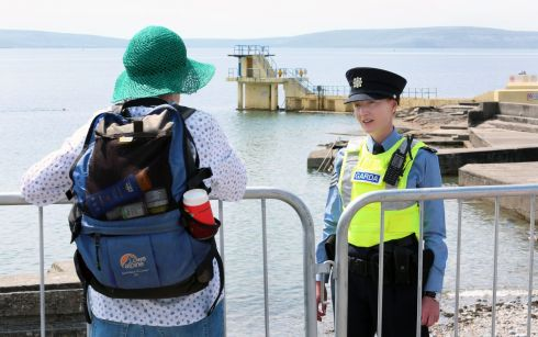 SWIMMING'S OUT: A garda explains to a woman the public closure of the Blackrock diving tower area, in Salthill, Galway, amid the continuing coronavirus pandemic. It follows the arrest of two people there on Saturday evening in an incident involving up to 40 teenagers. Photograph: Joe O'Shaughnessy