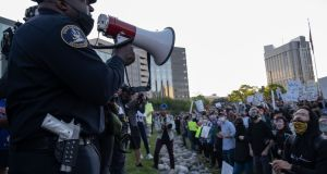 Police officers speak to demonstrators in front of the police station in Detroit, Michigan. Photograph: Seth Herald/AFP via Getty Images