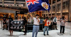 Pro-democracy protester  waves a British colonial flag during a  rally at a shopping mall in the Central district in Hong Kong. Photograph: Isaac Lawrence / AFP via Getty Images