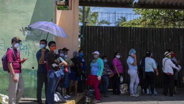 Relatives of coronavirus patients wait to take them food at a hospital in Managua, Nicaragua. Photograph: Inti Ocon/The New York Times
