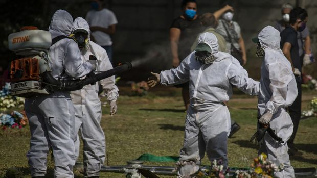 Gravediggers are disinfected after burying a body in Managua. Photograph: Inti Ocon/The New York Times