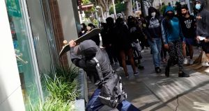 A man attempts to break the window of a store with a skateboard during widespread protests  in Santa Monica, California on Sunday. Photograph:  Warrick Page/Getty Images