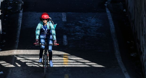 A woman rides her bike, in Bogota, Colombia, where the government is closing 120km of streets to car traffic. Phototgraph: Luis Acosta/AFP via Getty Images