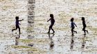 Children  playing the in low tide on Dollymount Strand. Photograph: Tom Honan/The Irish Times.