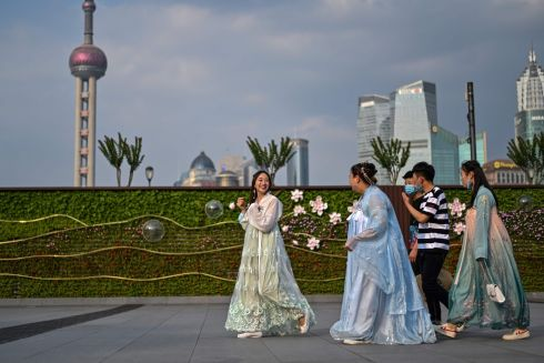 SHANGHAI SURPRISE: Young women in traditional costumes walk along a stretch known as the Bund, situated alongside the Huangpu River, in Shanghai, China. Photograph: Hector Retamal/AFP/Getty