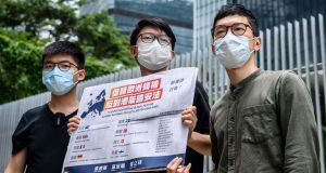 Pro-democracy party Demosisto members (L-R) Joshua Wong, Sunny Cheung and Nathan Law, hold a placard urging European leaders to act against a national security law during a press conference outside the Legislative Council in Hong Kong on Wednesday. Photograph: Antony Wallace/AFP via Getty Images