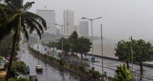 Motorists drive on a road near the Marine Drive under heavy rain in Mumbai on Wednesday. Photograph: Punit Paranjpe/AFP/Getty Images