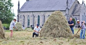 Kevin Fay teaches his grandson Darragh Freehill the centuries-old art of twisting a hay rope as they make cocks of hay at St Marys church, Staghall, Co Cavan. Parishoners Kevin, Darragh, along with Austin McGurren and Jim Tully turned up at the church to cut the cemetry grass.  Photograph: Lorraine Teevan
