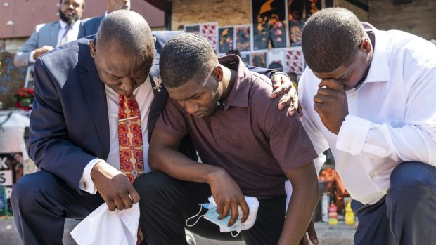 Quincy Mason Floyd (centre), son of George Floyd, and attorney Ben Crump (left) kneel on Wednesday at the site where Floyd was killed, in Minneapolis, Minnesota. Photograph: Stephen Maturen/Getty Images