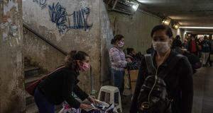 People wear face masks in São Paulo, Brazil amid the coronavirus pandemic. Photograph: Victor Moriyama/The New York Times