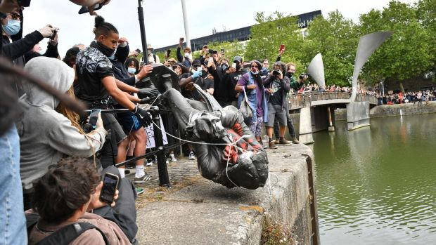Protesters throw statue of Edward Colston into Bristol harbour during a Black Lives Matter protest rally on Sunday. Photograph: Ben Birchall/PA Wire