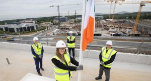 Hines marked the official capping out of its first new apartment block at Cherrywood yesterday with the raising of the Irish flag above the site. Pictured are Hannah Ward, a health and safety officer at Sisk in Cherrywood, raising the flag watched (left to right) by Donal McCarthy, chief operating officer (Ireland and Europe) John Sisk & Son, Gary Corrigan, managing director, Hines and Brian Moran, senior managing director at Hines