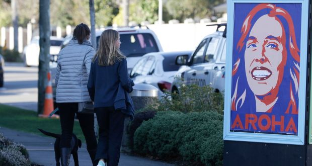 Pedestrians walk past a billboard featuring New Zealand prime minister Jacinda Ardern  in Christchurch, New Zealand. Photograph: Mark Baker/AP