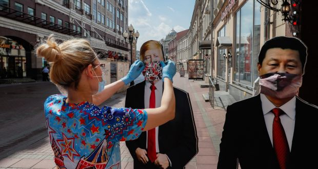 A gift shop worker sets up cardboard cutouts of  US president Donald Trump  and Chinese president Xi Jinping on the street after reopening a shop in Moscow, Russia. Moscow authorities are easing coronavirus restrictions. Photograph: Yuri Kochetkov/EPA
