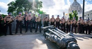 Minnesota State Troopers surrounded the statue of Christopher Columbus after it was toppled in Minnesota. Photograph: Leila Navidi/Star Tribune via AP