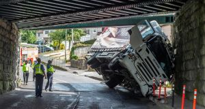 A truck which struck a railway bridge lies trapped at Dublin Hill, Cork city today. Photograph: Michael Mac Sweeney/Provision