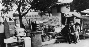 1937, Los Angeles: An evicted couple sits on the curb surrounded by their belongings during the Great Depression. Photograph:  American Stock/Getty