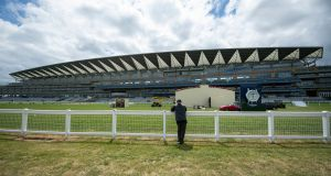 A member of the public looks on as the finishing touches are made at Ascot Racecourse. The Royal Ascot meeting will take place behind closed doors between Tuesday June 16th and Saturday June 20th. Photo: Edward Whitaker/PA Wire