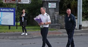 Members of the fire service carry flowers to the scene in Castlerea, Co Roscommon, where Det Gda Colm Horkan was shot dead on Wednesday night. Photograph: Niall Carson/PA Wire