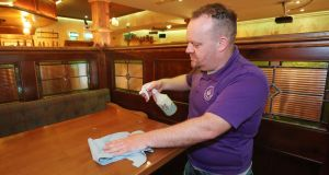 Pubs reopening: barman Mark Ennis disinfects tables at O'Gorman's in Portlaoise. Photograph: Niall Carson/PA Wire