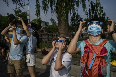 A Chinese man and girl  wear protective masks to prevent COVID-19 and protective glasses as they watch the sun during the annular solar eclipse outside the Forbidden City on June 20, 2020 in Beijing, China. The eclipse's path of totality, when the earth, moon and sun are aligned, passed from west to east over 12 countries and coincided with the arrival of the summer solstice. Photograph Kevin Frayer/Getty Images