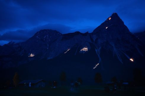 Fires illuminate the slopes of the Wetterstein and Mieming mountain ranges near Ehrwald, Austria, 20 June 2020. The custom of celeberating summer solstice and the birthday of John the Baptist with festive fires has a long history in the alpine regions of Europe.  Photograph Philipp Guelland/EPA