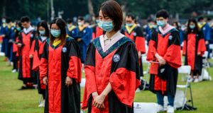 University  graduates standing in silent tribute for victims of the Covid-19 coronavirus during their graduation ceremony in Wuhan University in Wuhan in China's central Hubei province on Saturday. Photograph: STR/AFP/Getty Images
