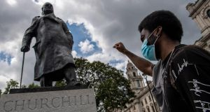 A protester raises his fist next to a statue of Winston Churchill in Parliament Square in London during a Black Lives Matter demonstration. Photograph: Chris J Ratcliffe/Getty Images