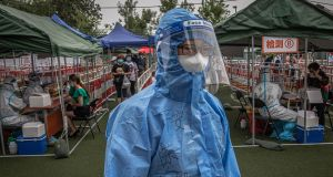 A worker wearing a full protective suit stands as people are tested for Covid-19 at a makeshift coronavirus testing centre, in Beijing on Wednesday. Photograph: EPA