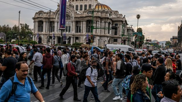 Pedestrians at a busy intersection by the Palacio Bellas Artes in Mexico City. Photograph: Victor Moriyama/The New York Times