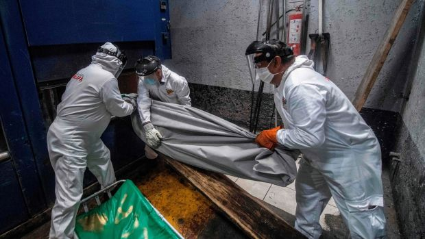 Employees put a body bag with the remains of a victim of Covid-19 in an oven at a crematorium in Mexico City. Photograph: Pedro Pardo/AFP via Getty Images