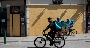 Deliveroo cyclists passing   boarded up premises  on Grafton Street, Dublin, earlier this year. Photograph: Gareth Chaney/Collins