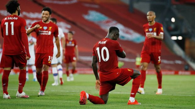 Sadio Mané takes a knee after scoring Liverpool's fourth goal in the Premier League game against Crystal Palace at Anfield. Photograph: Phil Noble/Pool via Getty Images