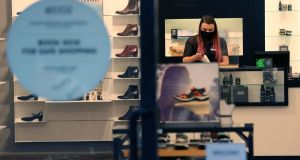 A staff member wearing a protective face mask in a shoe shop in Belfast. File photograph: Brian Lawless/PA