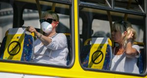 A passenger wears a mask on board a bus. Photograph: Crispin Rodwell/ The Irish Times