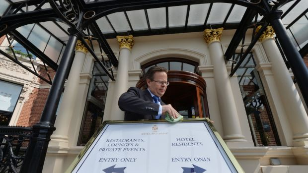 Shelbourne Hotel manager Lucius Farrell adjusting Covid-19 signage outside the hotel. Photograph: Alan Betson