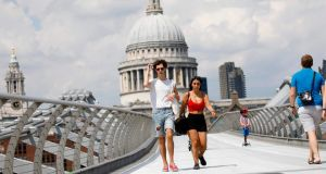 A couple walk over The Millennium Bridge away from St Paul's Cathedral in London.  Britons have been   urged to abide by social distancing rules over fears over a coronavirus resurgence. Photograph: Tolga Akmen/AFP via Getty