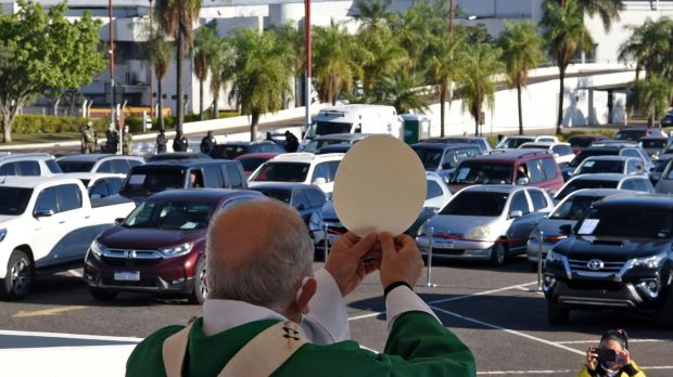 Archbishop officiates a drive-in mass at the Silvio Pettirossi International Airport parking in Paraguay. Photograph: Norberto Duarte/AFP/Getty Images.