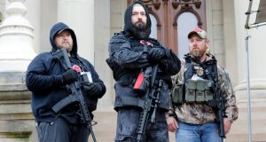 "Armed protesters  take part in an ""American Patriot Rally"",  organised by Michigan United for Liberty,  demanding the reopening of business in Lansing, the capital city of the state.  Photograph: Jeff Kowalsky/AFP/Getty Images"