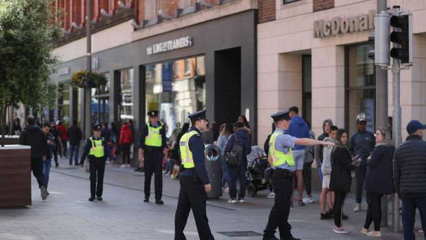 Gardaí on Dublin's Henry Street as people queue to enter JD Store on June 8th, the first day of re-opening of non-essential retail stores. Photograph: Nick Bradshaw for The Irish Times