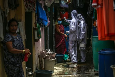 CORONAVIRUS: An Indian health worker checks the temperature, blood oxygen and heart rate of a resident in Appa Pada area, a Covid-19 hotspot, in Mumbai. Photograph: Divyakant Solanki/EPA